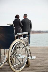 Rollstuhl plus Mann und Frau im Hintergrund